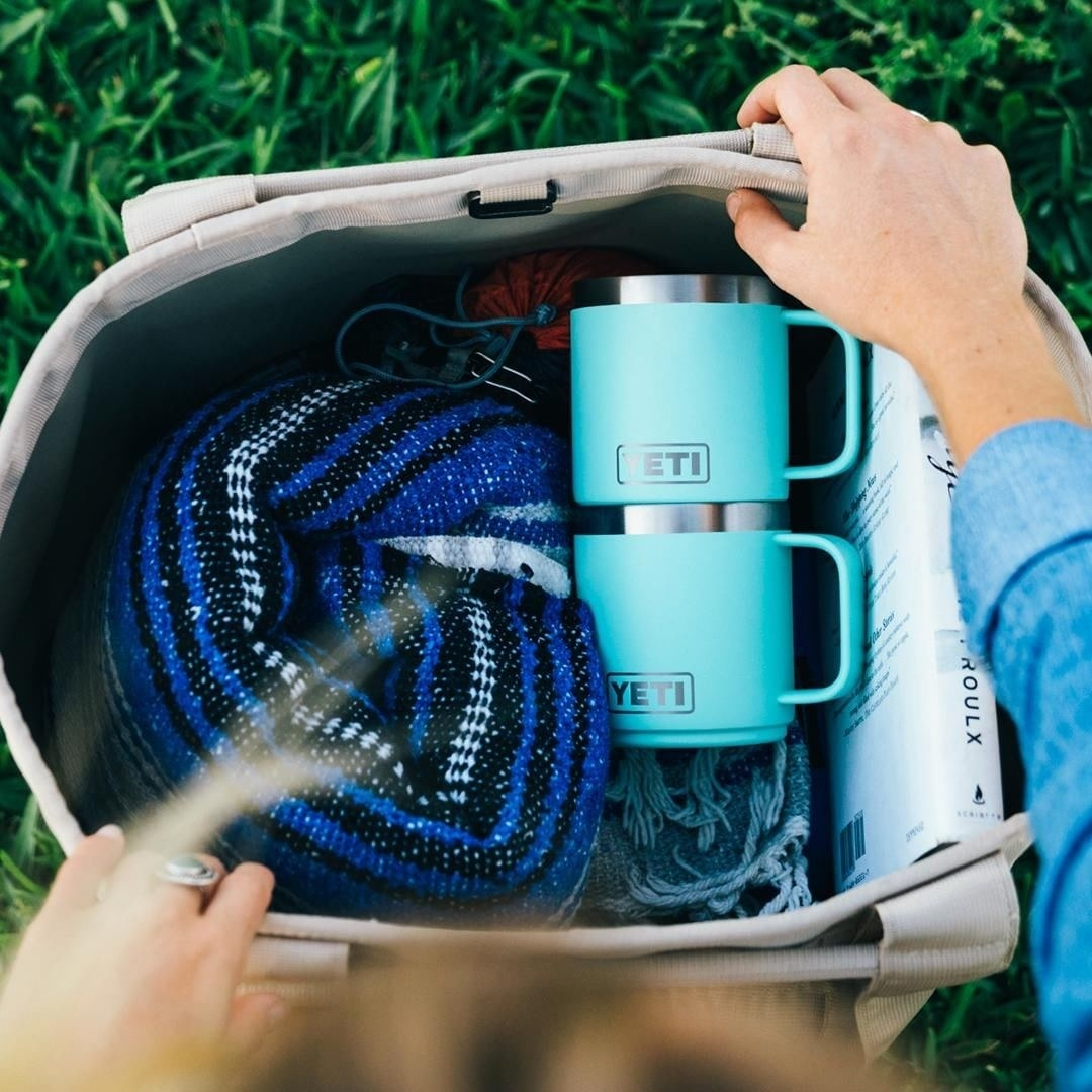 A person opening a bag with two YETI mugs, a blanket, and a book inside of it