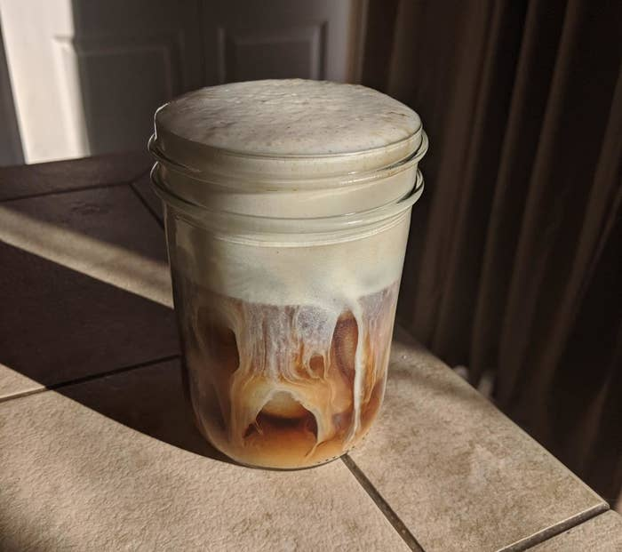 a mason jar with iced coffee and thick foam