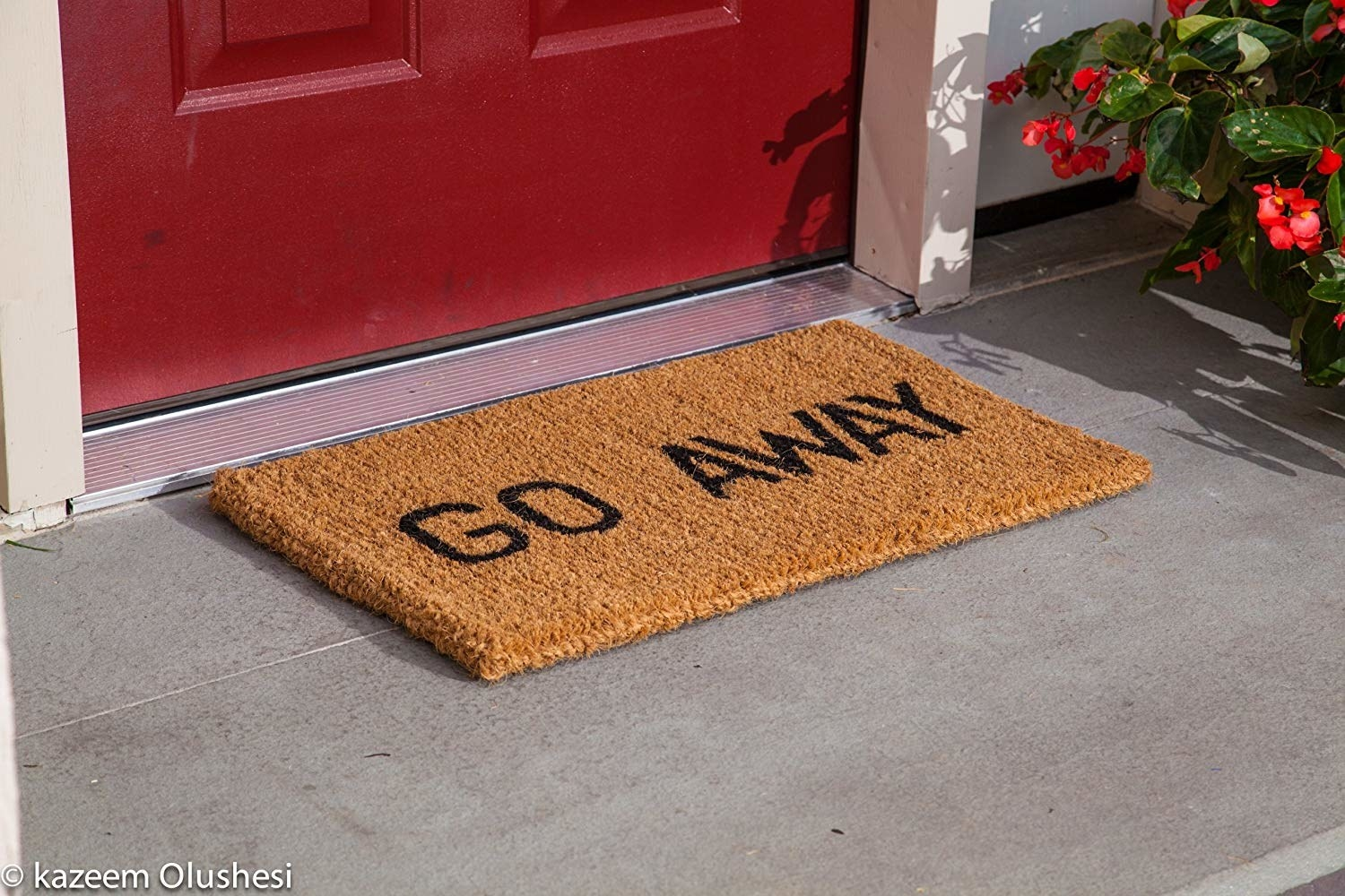 """a sturdy doormat with """"go away"""" on it in black letters"""