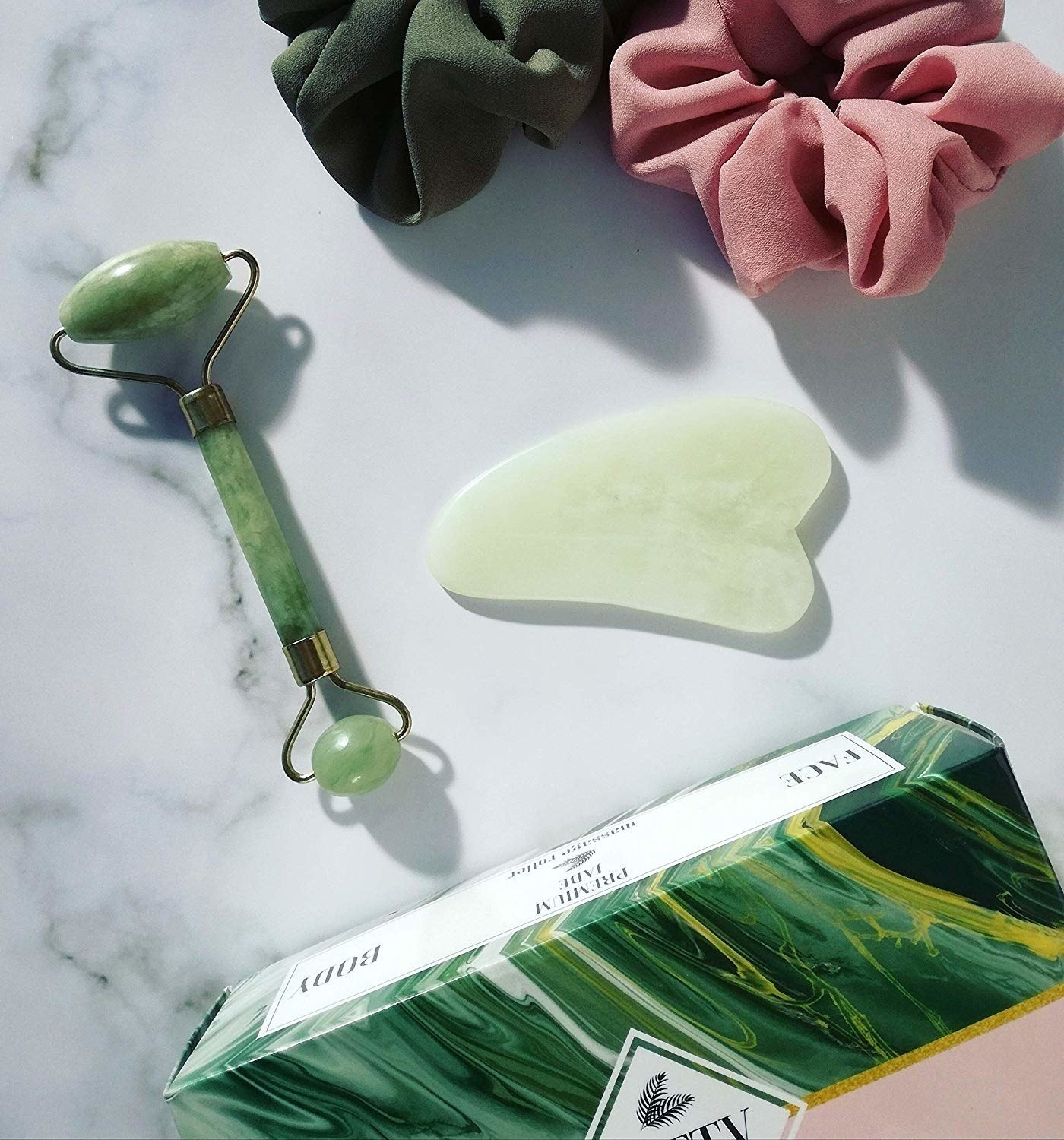 the green jade roller and gua sha set next to two hair scrunchies