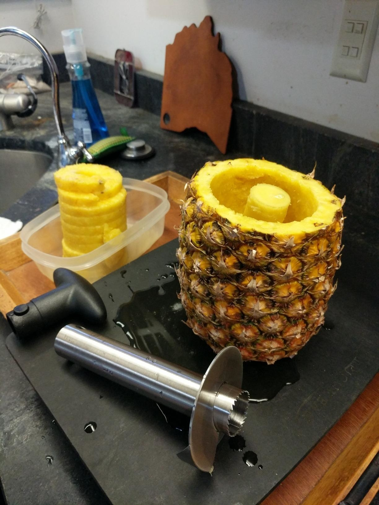The tool on a counter with the cored pineapple shell and spiral-cut fruit in a container