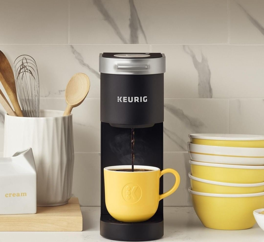 A tall, but slim Keurig coffeemaker with a cup of coffee sitting on the base placed on a counter