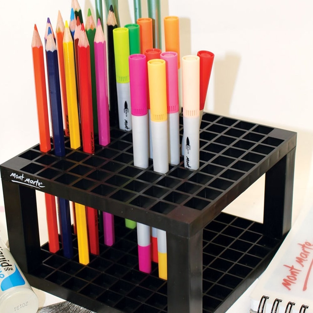A plastic cube with pencils and markers sitting upright