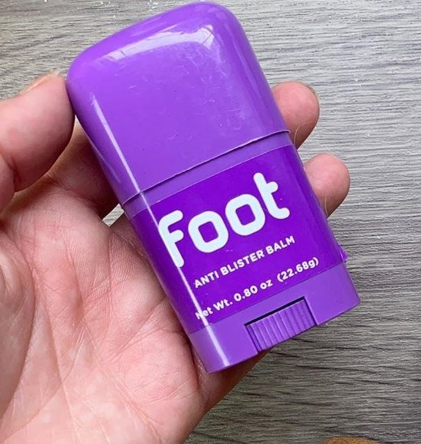 hand holding purple tube labeled