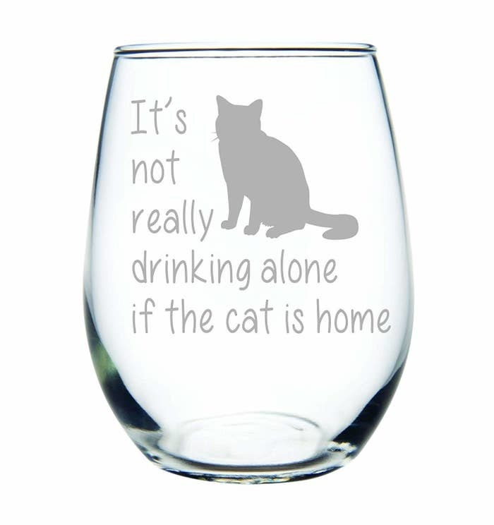 "a stemless wine glass with a cat on it that says ""it's not really drinking alone if the cat is home"""