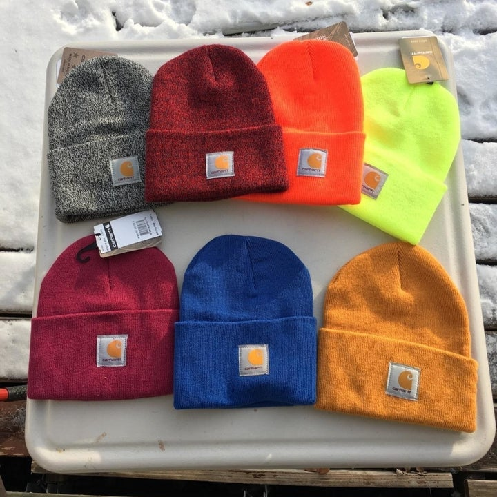 reviewer's pile of hats in seven colors