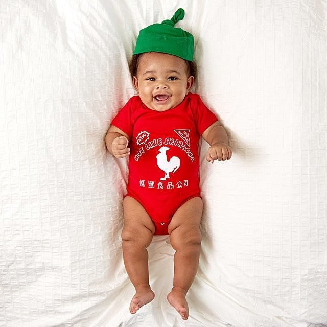 Baby wearing hot sauce onesie with green cap hat