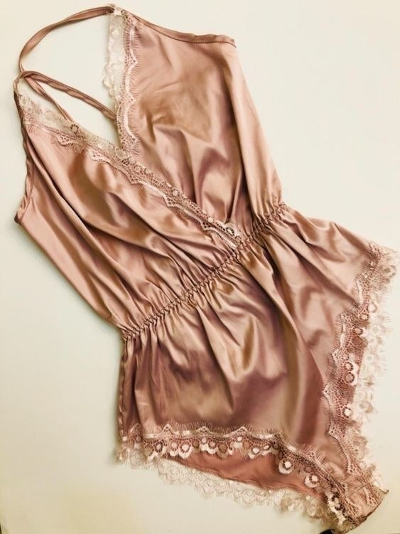 a reviewer's pink satin romper with eyelash lace on the edges