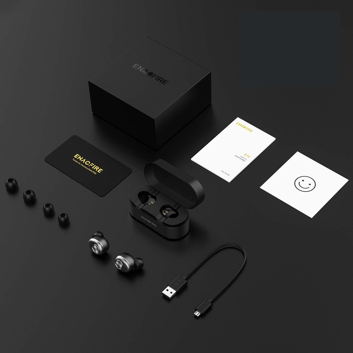A flatlay of all the elements of the headphones, including a charging cable and two sets of replacement earpieces.