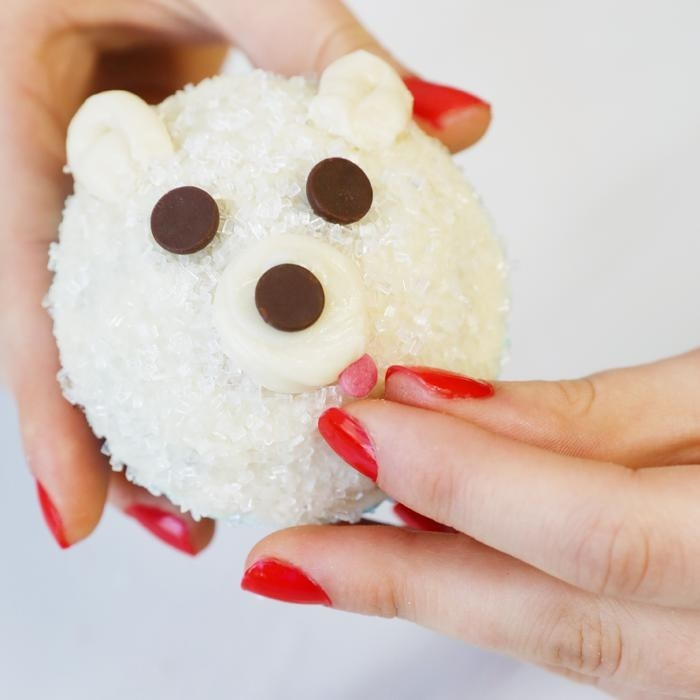 A baked good shaped like a polar bear with chocolate chips for eyes and nose