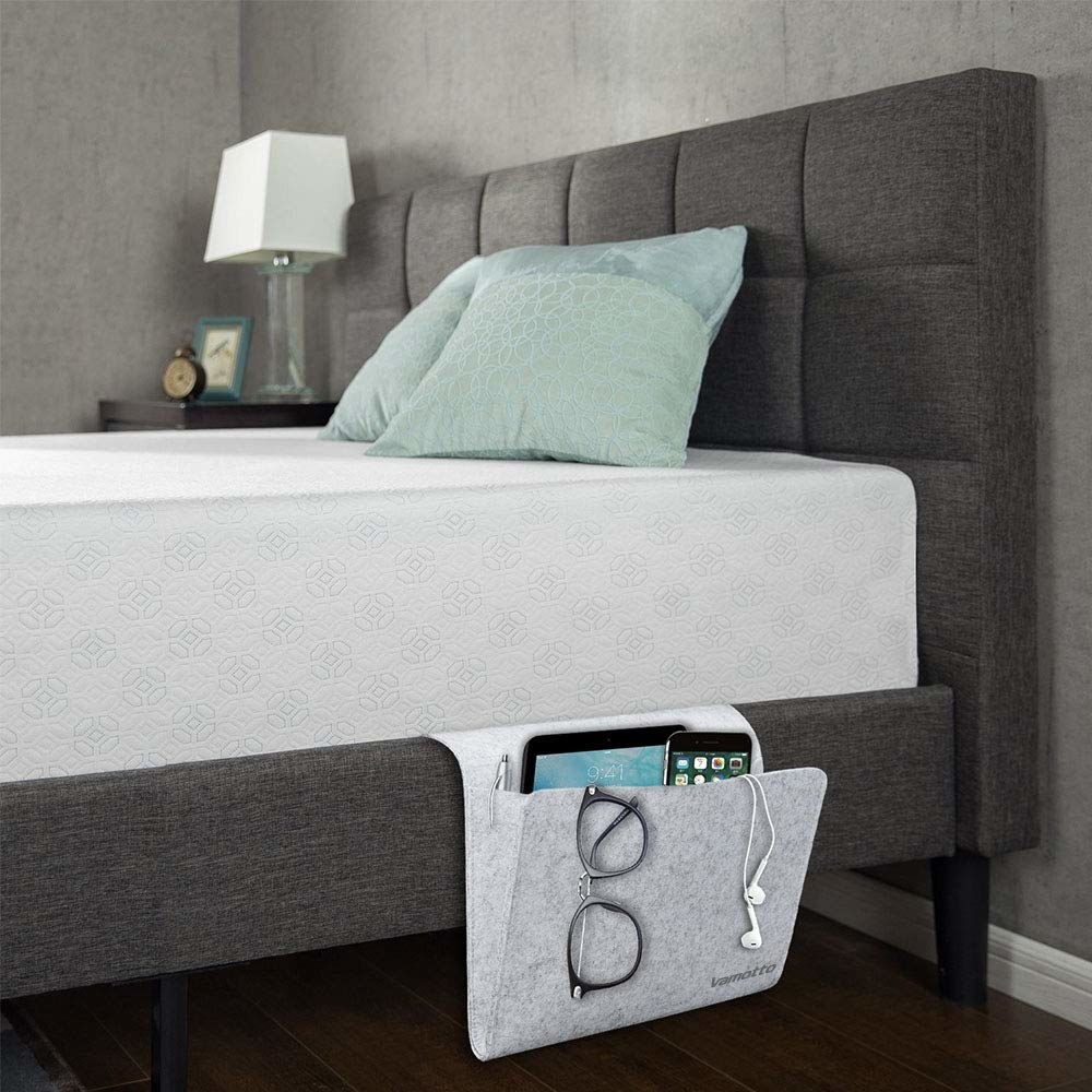 A small felt folder hanging from a bed frame and filled with a tablet, cell phone, pen and glasses