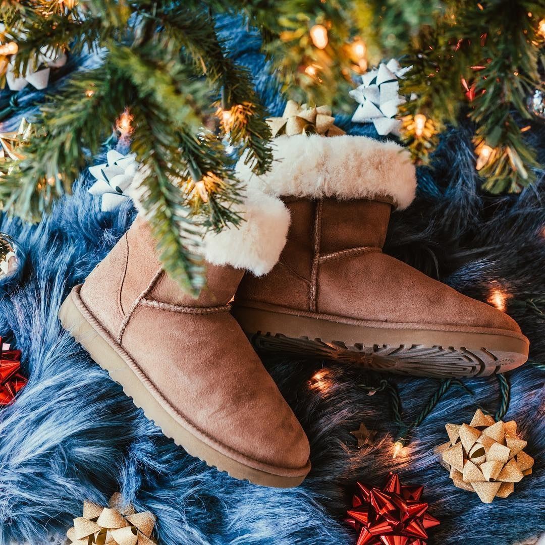 A pair of Ugg boots under a tree surrounded by bows