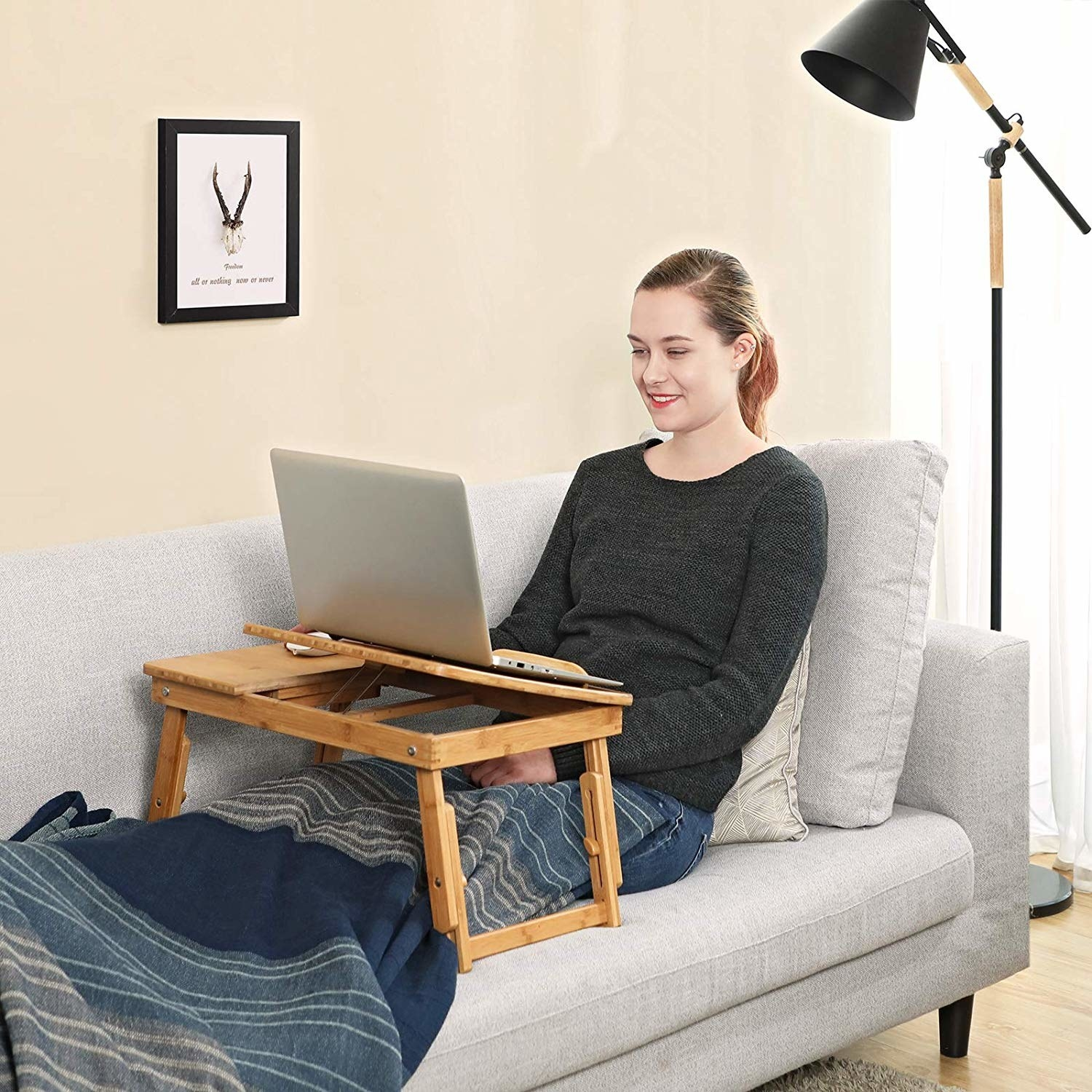 model using laptop desk on couch