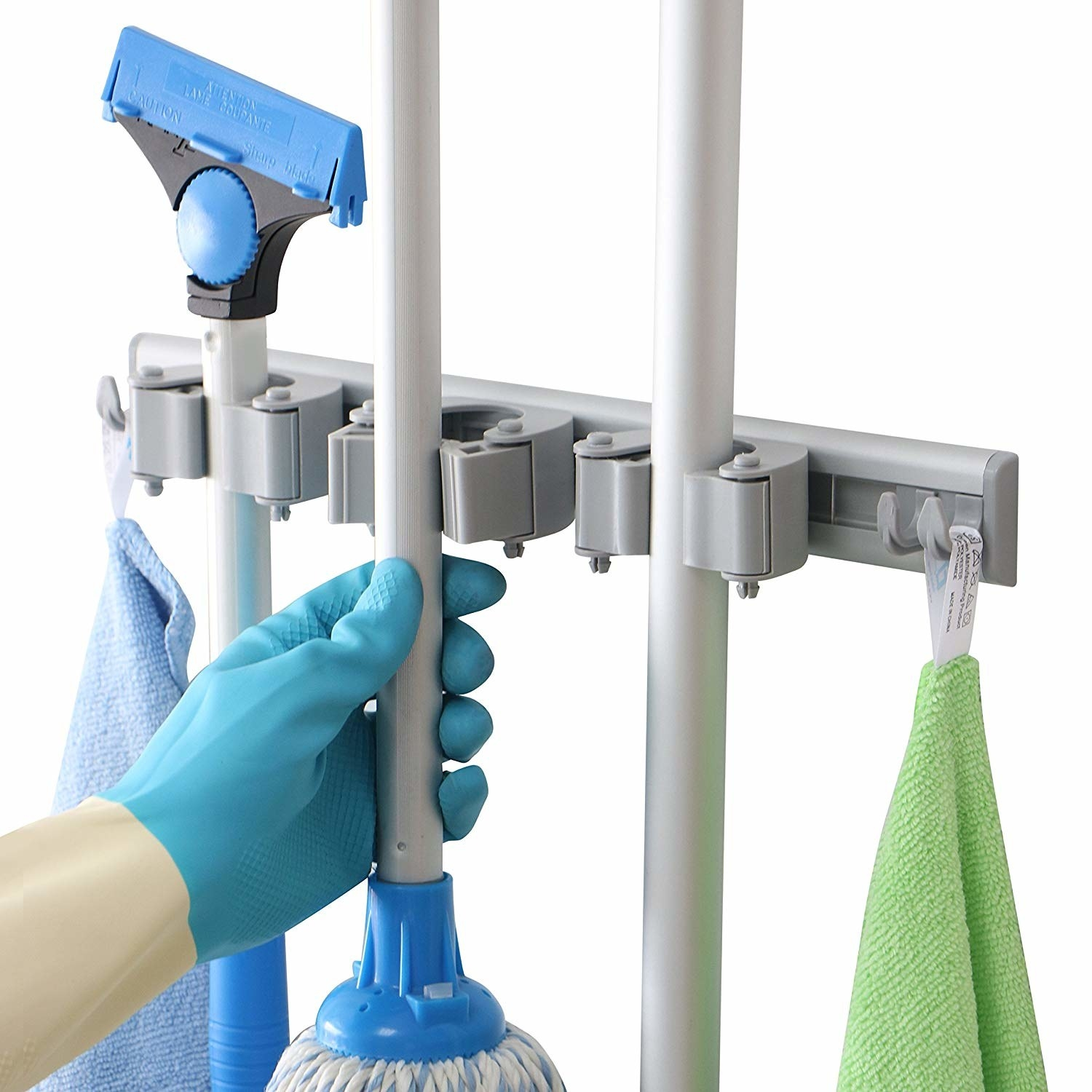 a hand reaches for a mop hanging from a mounted dr dirt mop and broom holder