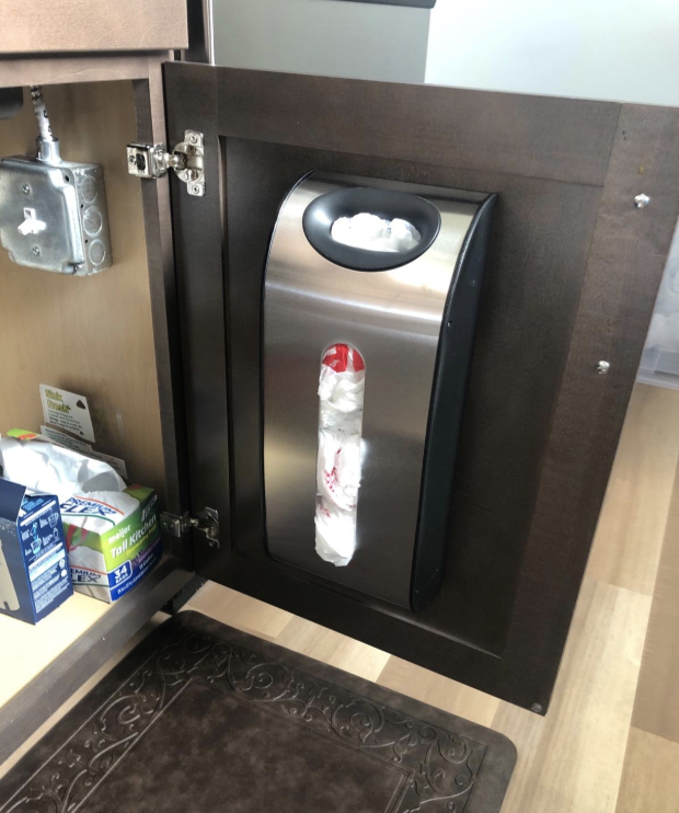 reviewer image of the simple human grocery bag dispenser mounted inside of a cabinet door