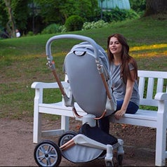 Person sitting on bench with stroller bed pushed into upright position