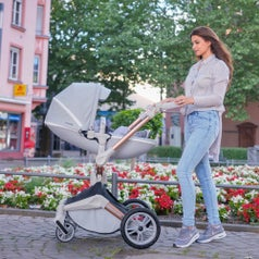 Person strolling baby in carriage. Baby is in laying position.