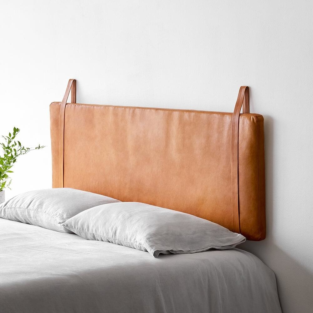 Rectangular leather headboard hanging from two leather straps on either side