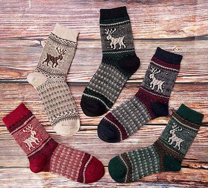 Going clockwise, the socks look like this: red print with a cream reindeer, cream print with a brown reindeer, dark green print with a cream reindeer, navy blue & red print with a cream reindeer, and a green & orange print with a cream reindeer.
