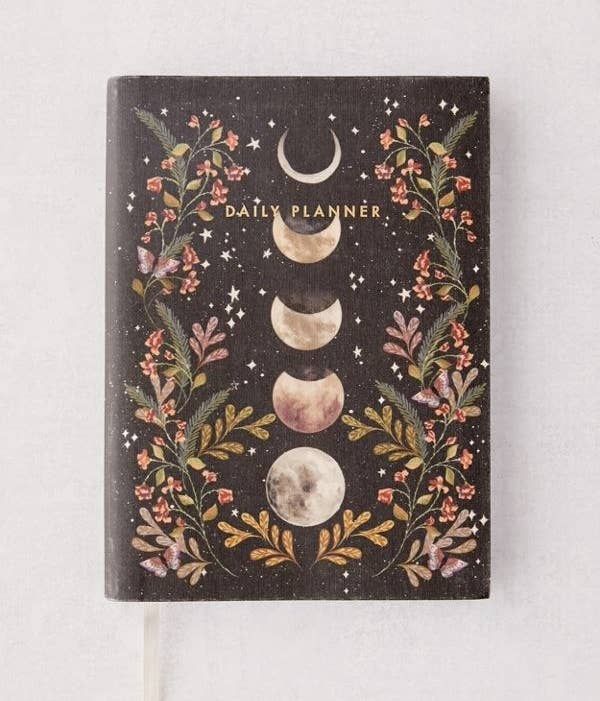 """The black notebook with illustrations of flowers and moon phases in the middle with the words """"Daily Planner"""" on top"""