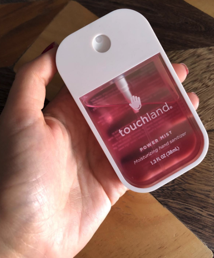 "A hand holds the sanitizer container. The container has a rectangular shape (like a cell phone but smaller) and the front is a transparent pink so the liquid inside (and how much you have left) is visible. It also says the brand name ""Touchland."""