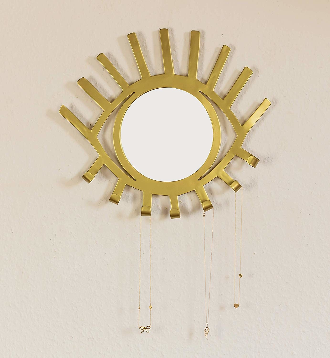 "circular mirror with gold eye-shape around it and the bottom ""eyelashes"" turned up into hooks with necklaces on them"