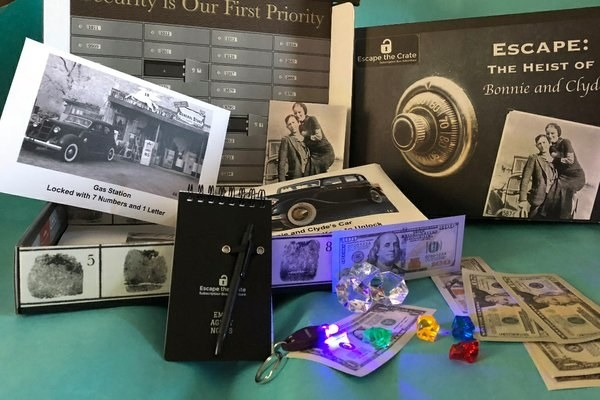 a Bonnie and Clyde themed box with dice, a notebook, fake money, and other objects