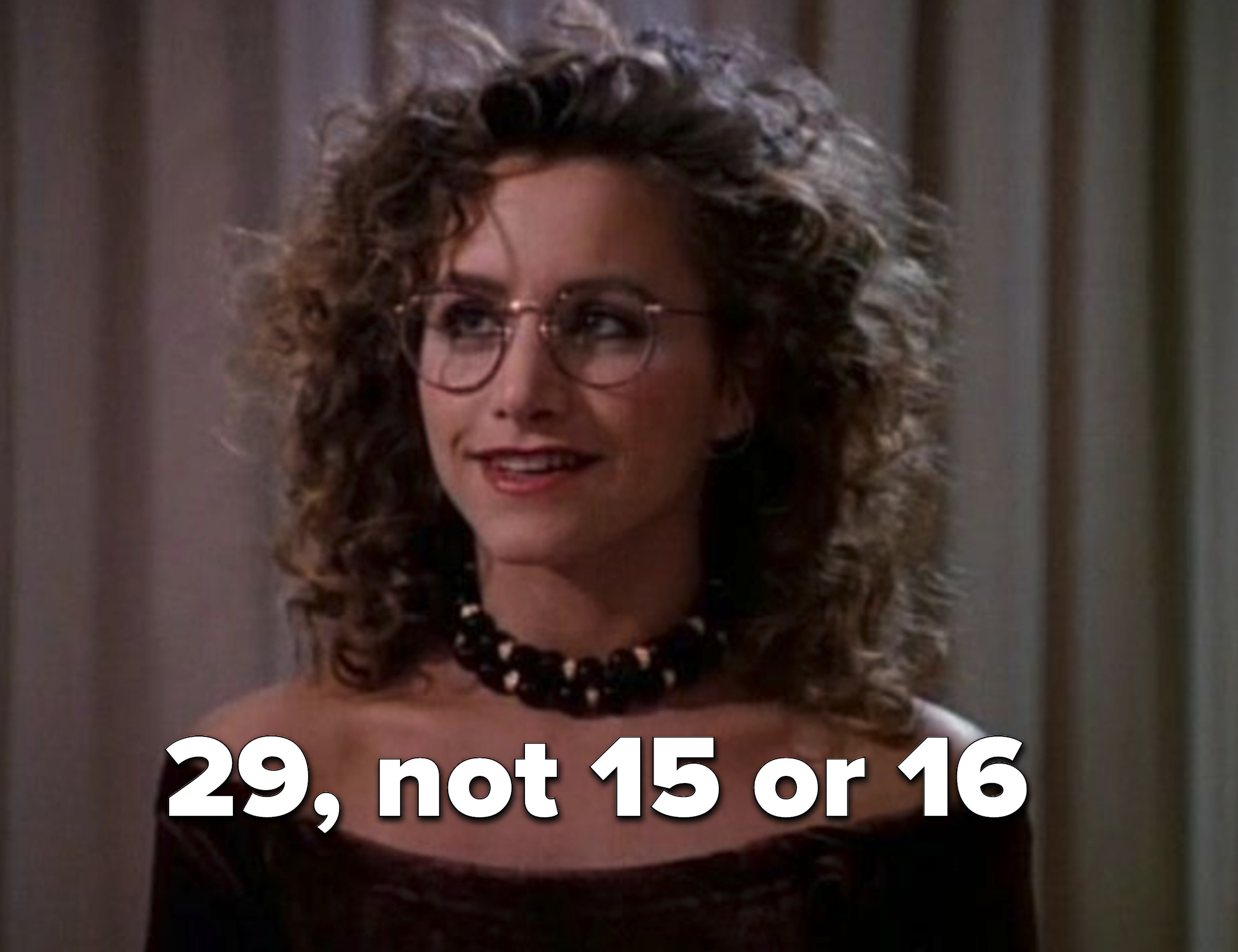 Andrea Zuckerman with a perm and '90s glasses
