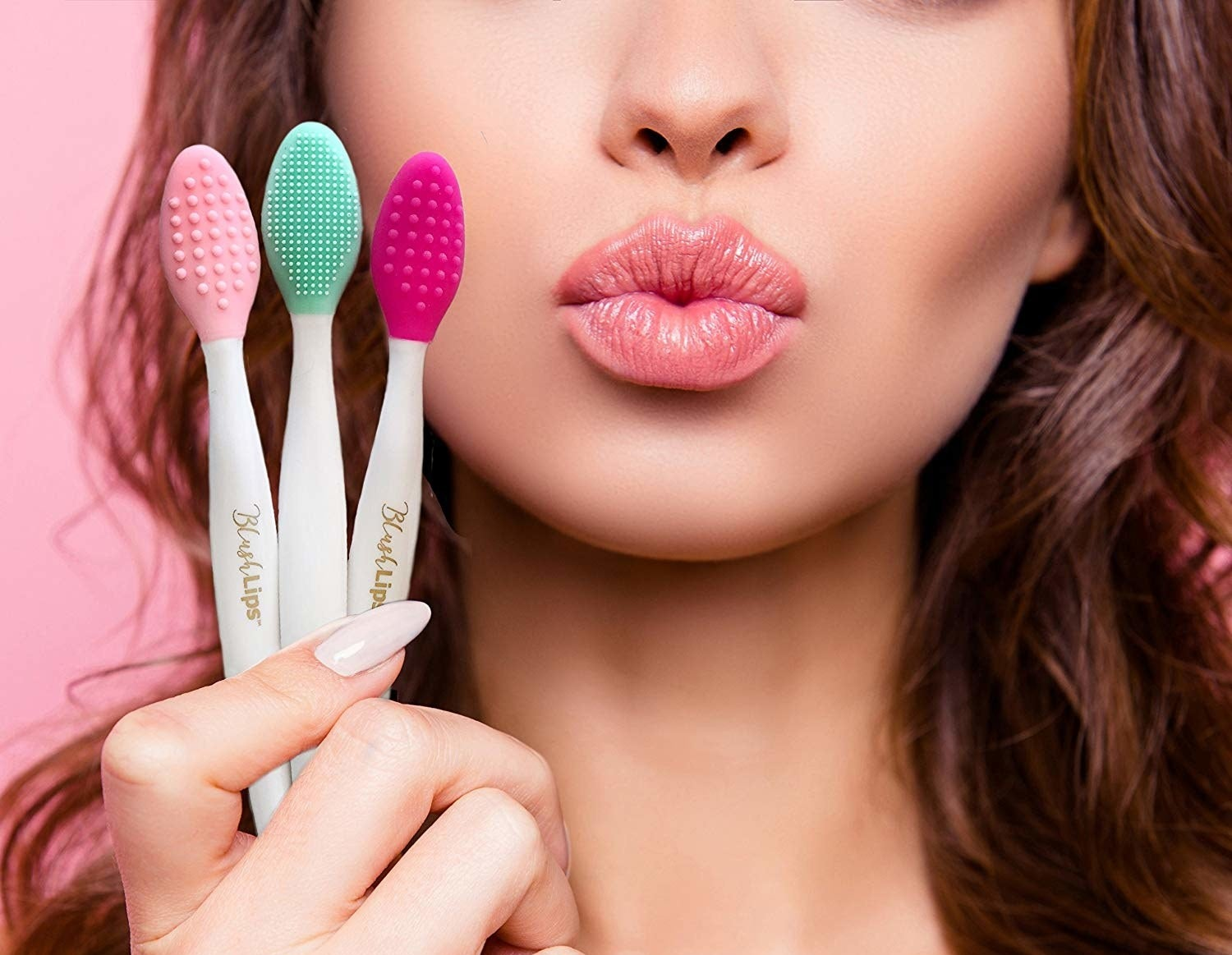 Person puckering lips while holding three toothbrush sized tools with silicone bumps for brushing lips