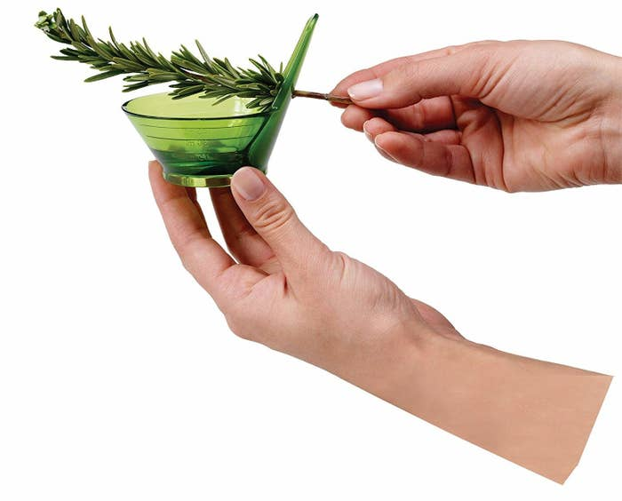 Hands pulling a twig of rosemary through the stripper