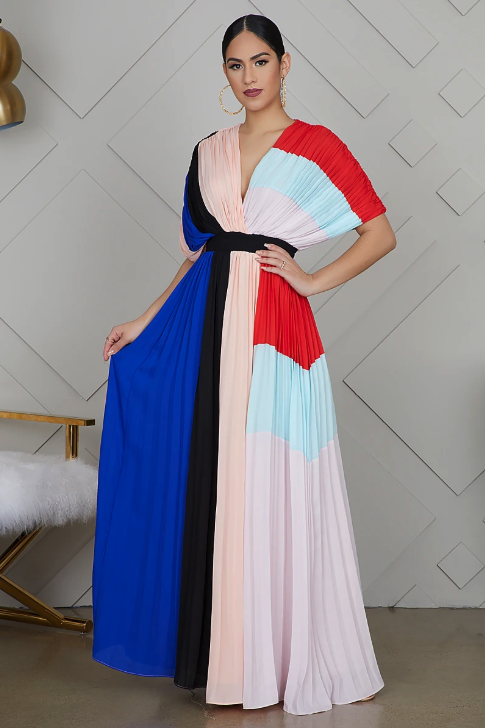 A woman wearing a long, pleated dress that is color-blocked with red, light blue, black, light pink, and blue.