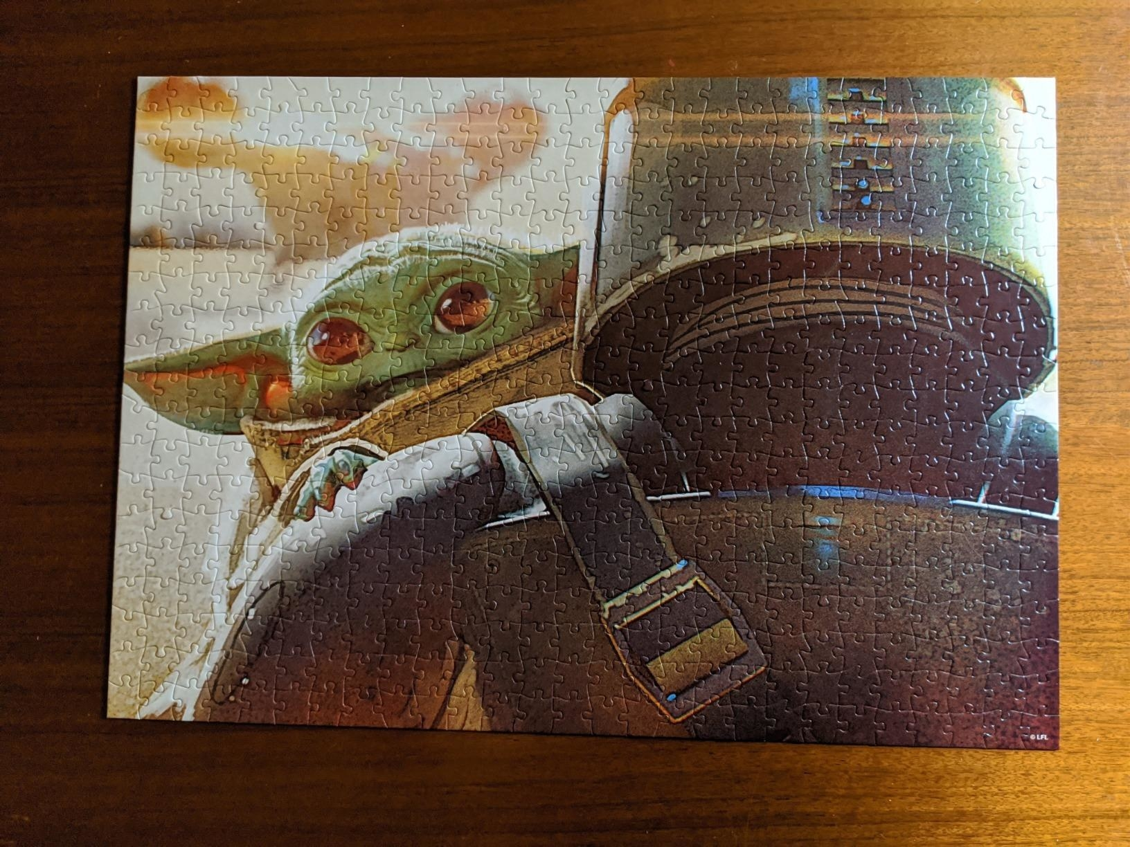 the assembled puzzle with the Mandalorian carrying Baby Yoda and Baby Yoda looking over his shoulder.