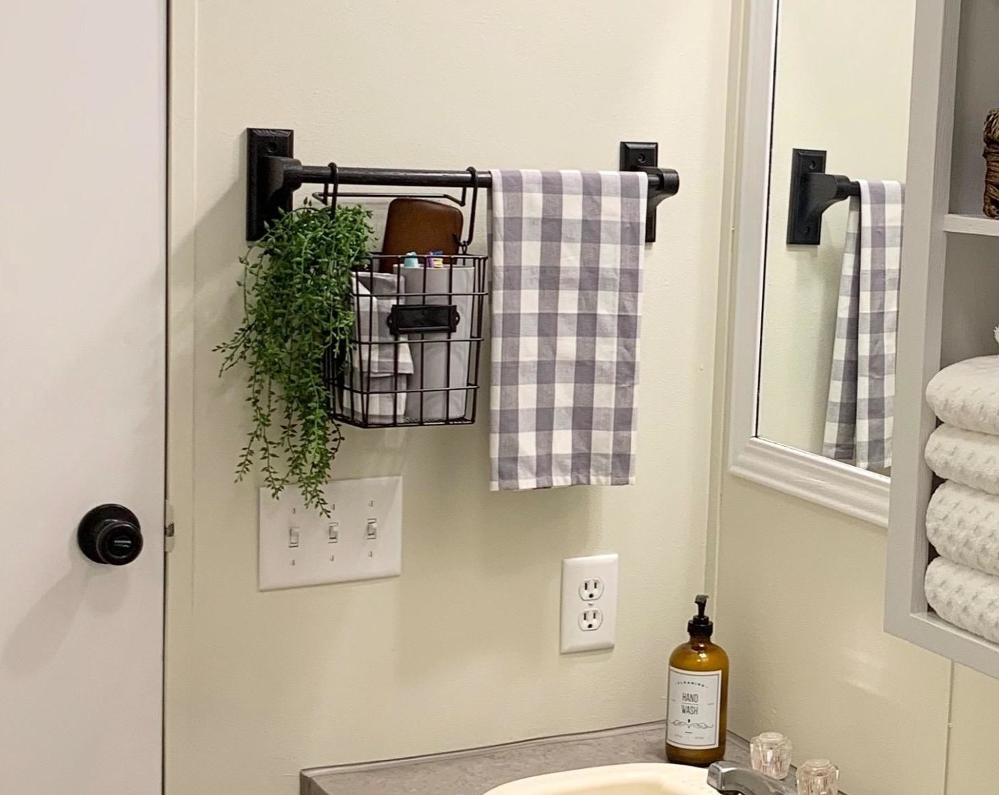 The basket hung from a towel bar and holding a variety of items as well as a plant