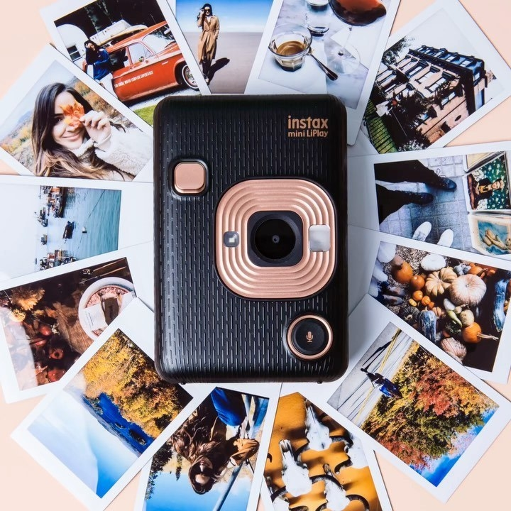 A camera surrounded by instant photos