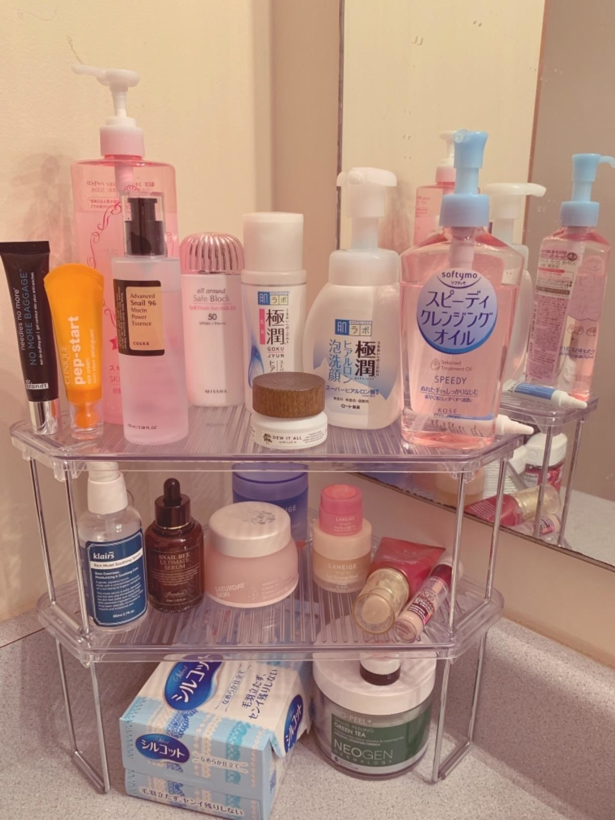 Reviewer image of the shelves stacked on top of each other and holding a variety of bathroom essentials
