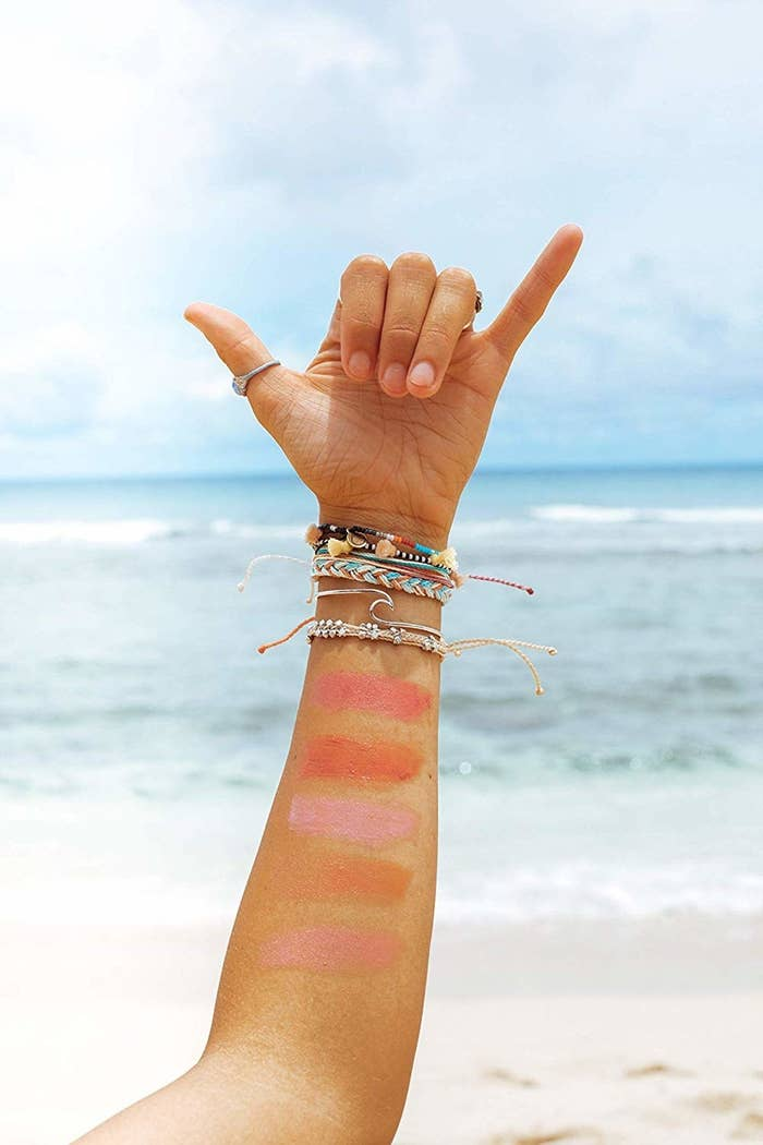 light skin tone  person's arm with five pink-y swatched lip colors