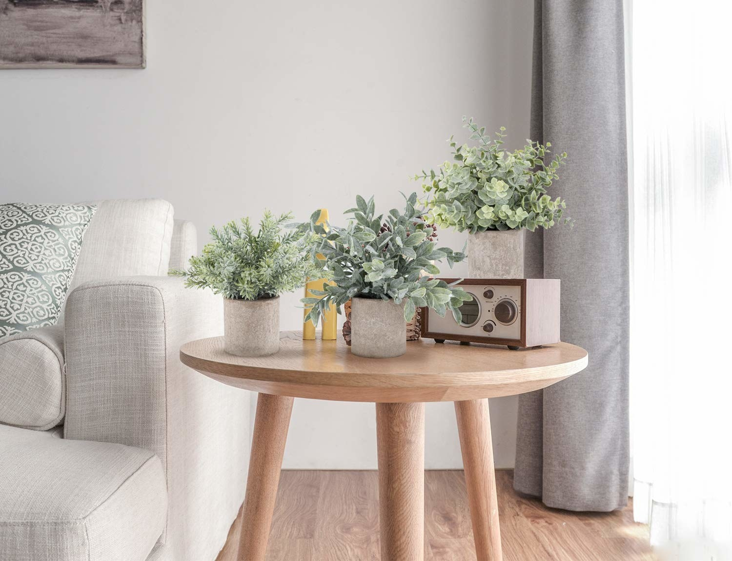 the three fake plants with different leaves in a tan round pot on a side table