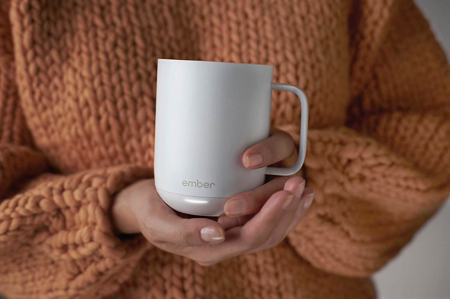 A person holding the mug in front of them