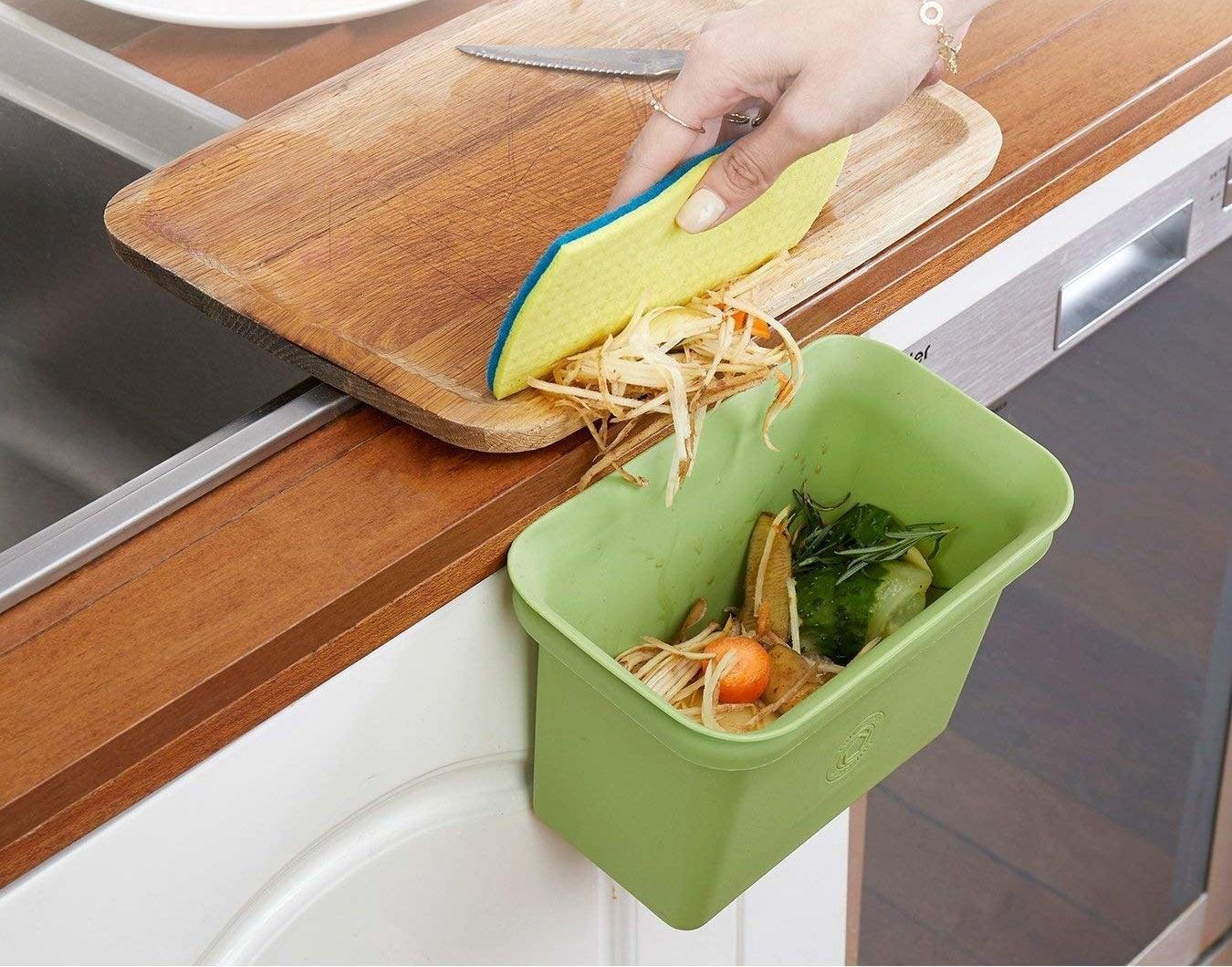 person swipes food scraps into bin