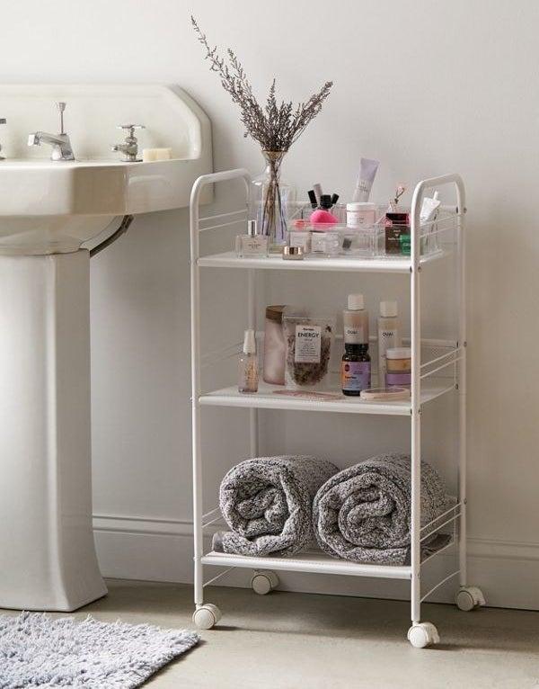 white three-tier shelf with wheels and assorted bathroom items on each shelf