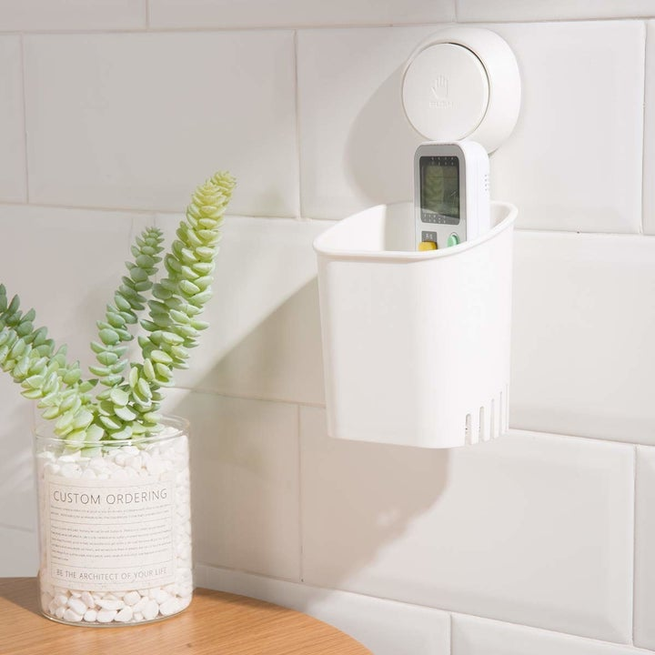 the white suction caddy hanging on the wall