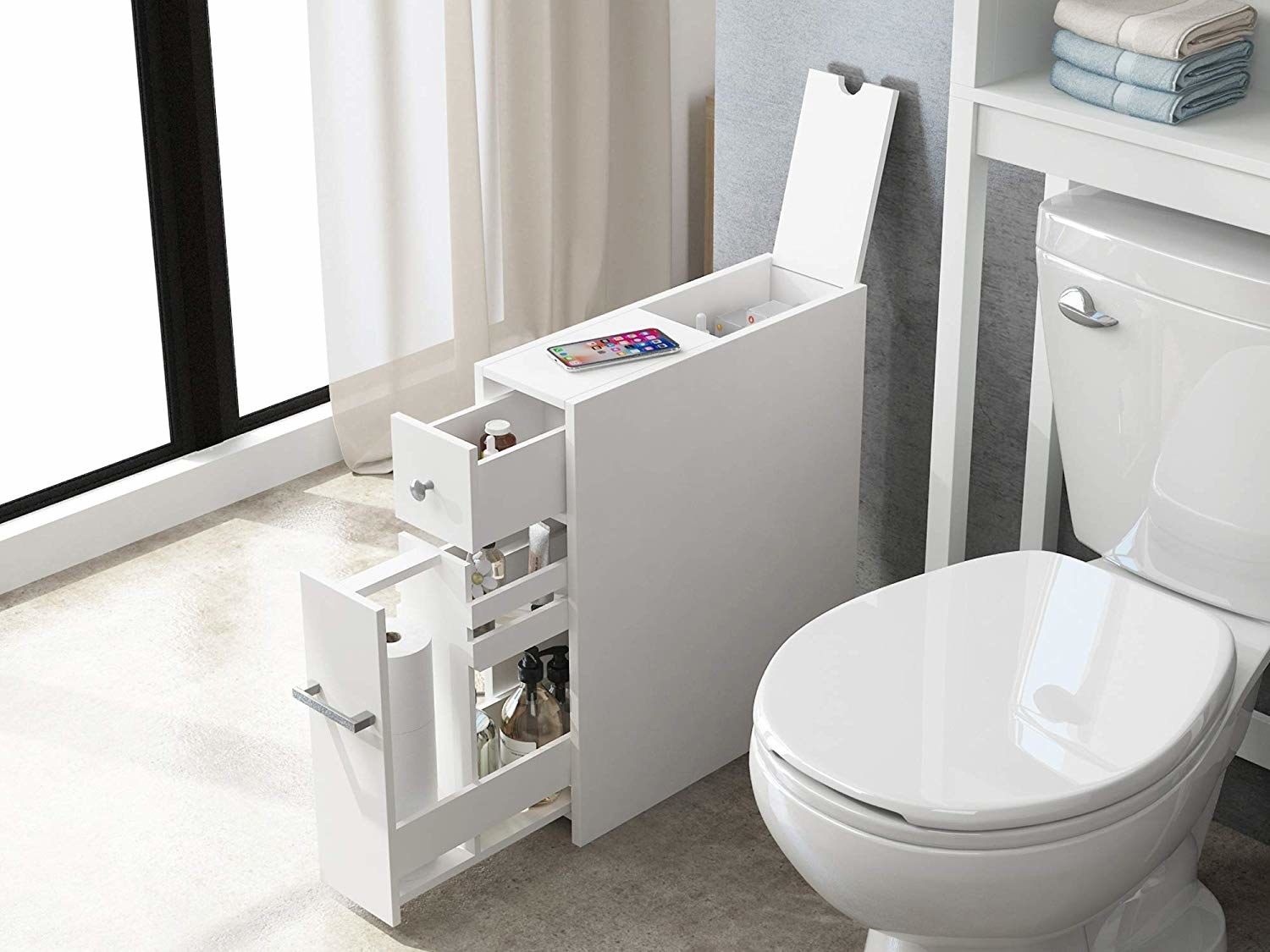 The cabinet with its drawers opened showing the variety of items it can store next to the toilet