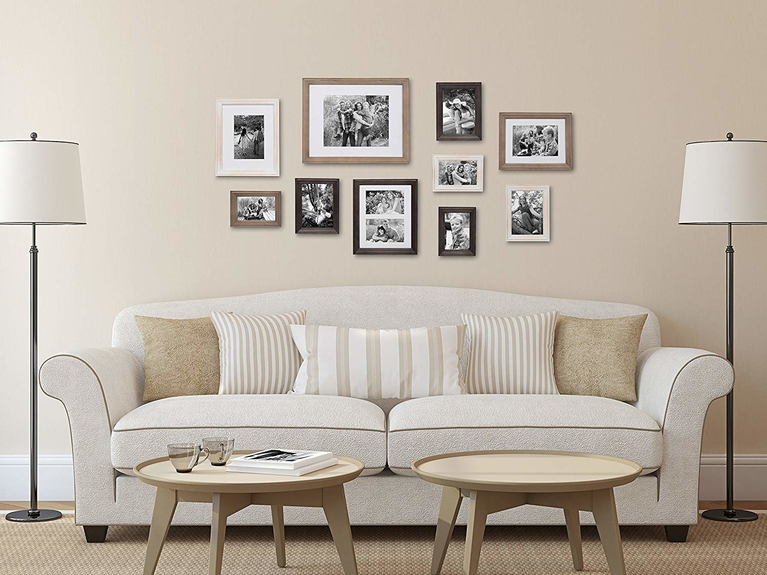 ten differently-sized frames on a wall over a couch arranged in a nice way