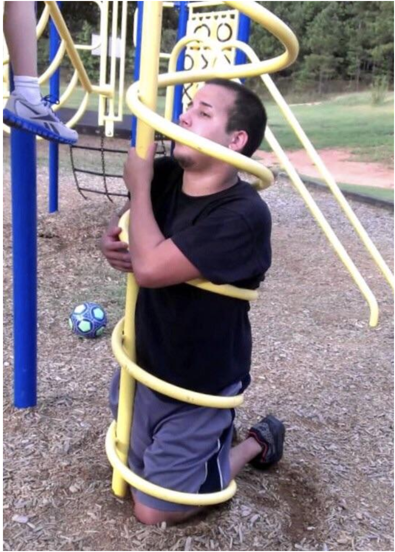 A man stuck between the bars of a playground toy