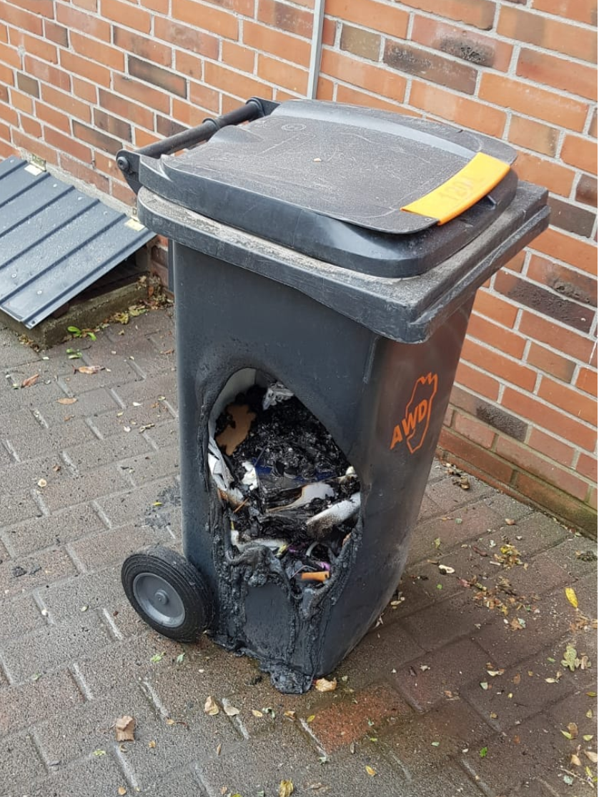 A trash can with a hole burned into the side