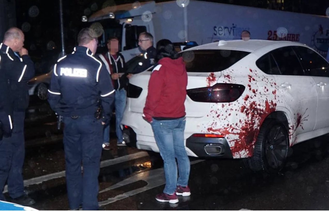 Police surround a car with a decal of blood splatters on the side