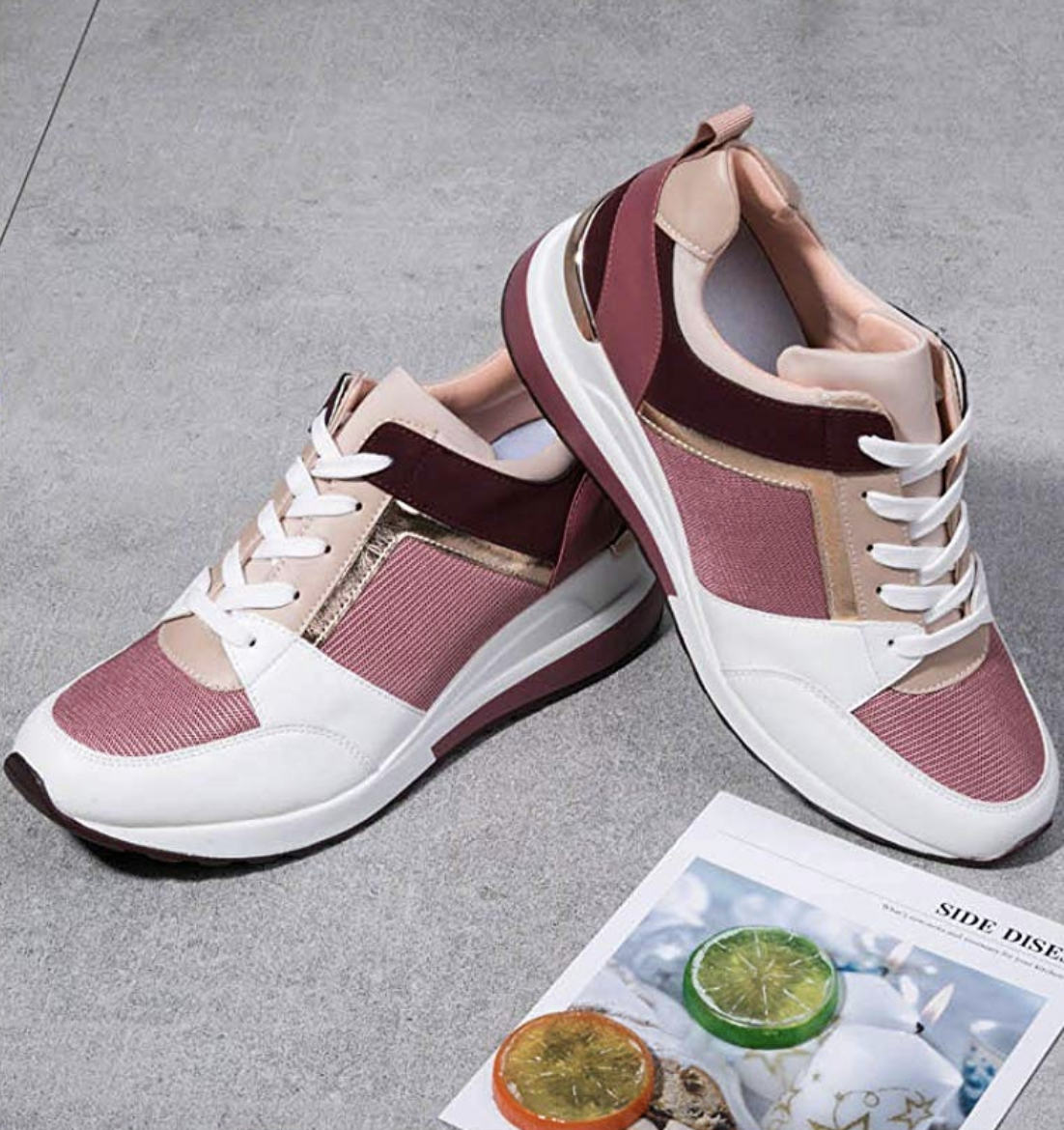 The sneaker with a wedge in the sole and patches of white, light pink, mauve, and burgundy throughout