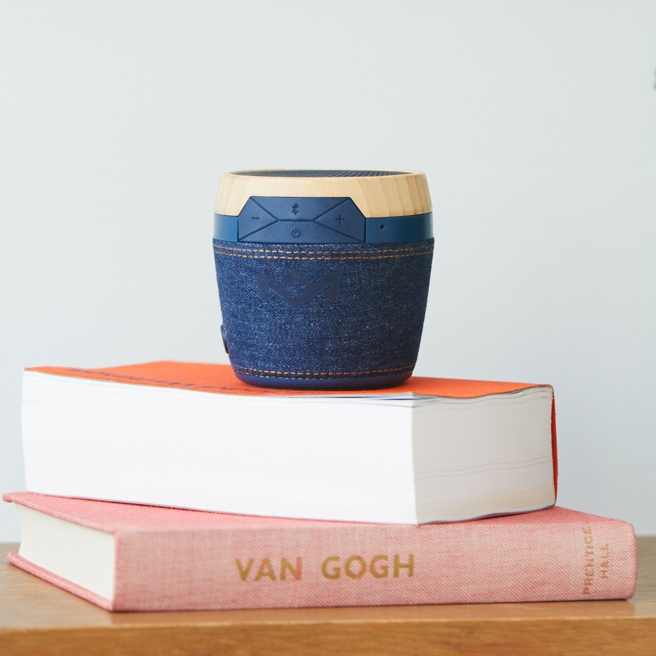 Denim-styled waterproof Bluetooth speaker on top of books