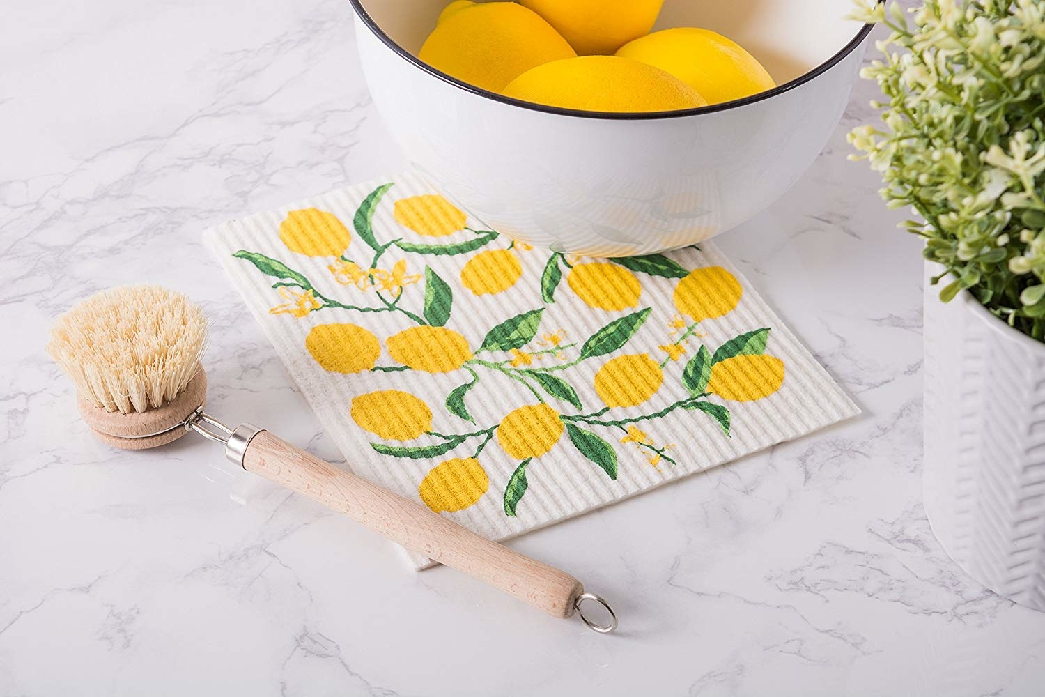 Lemon-patterned white dish cloth resting next to dish scrubber and bowl of lemons