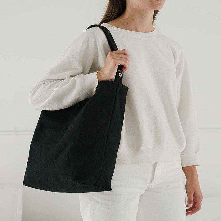 Black canvas tote thrown over model's shoulder